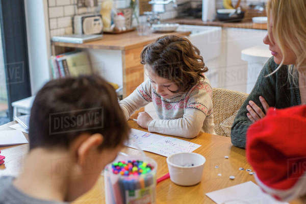 Three children and an adult woman at a table, drawing and writing cards and letters to Santa.  Royalty-free stock photo