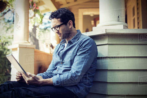A man sitting relaxing in a quiet corner of a porch, using a digital tablet.  Royalty-free stock photo