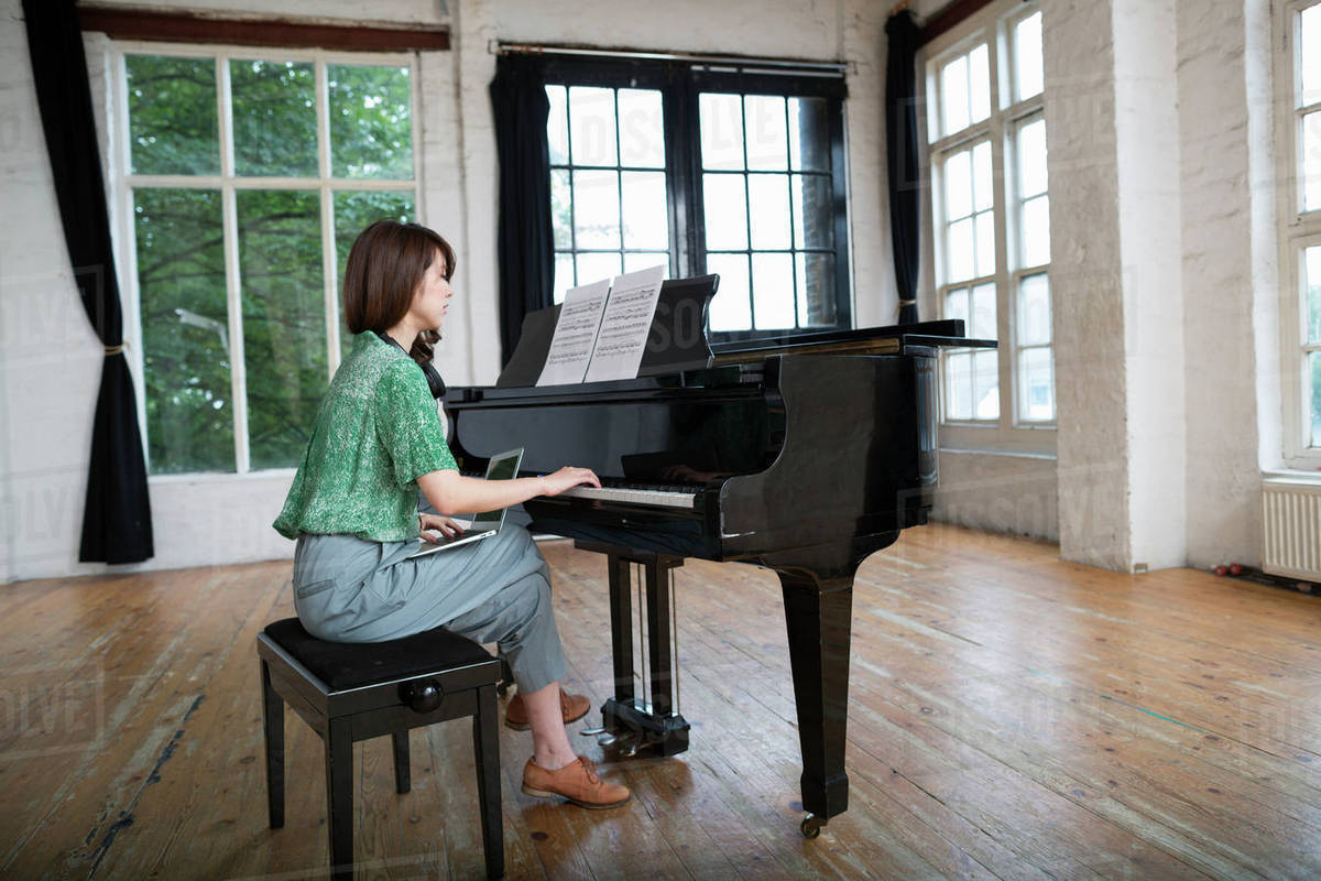 Young woman playing on a grand piano in a rehearsal studio. - Stock Photo - Dissolve