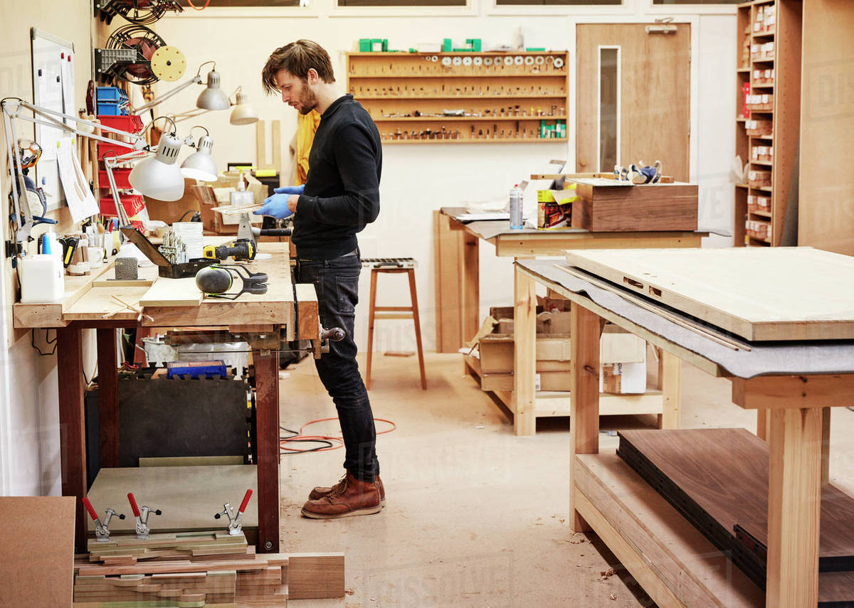 A furniture workshop making bespoke contemporary furniture pieces using  traditional skills in modern design. A man standing at a workbench holding  and examining an object. - Stock Photo - Dissolve