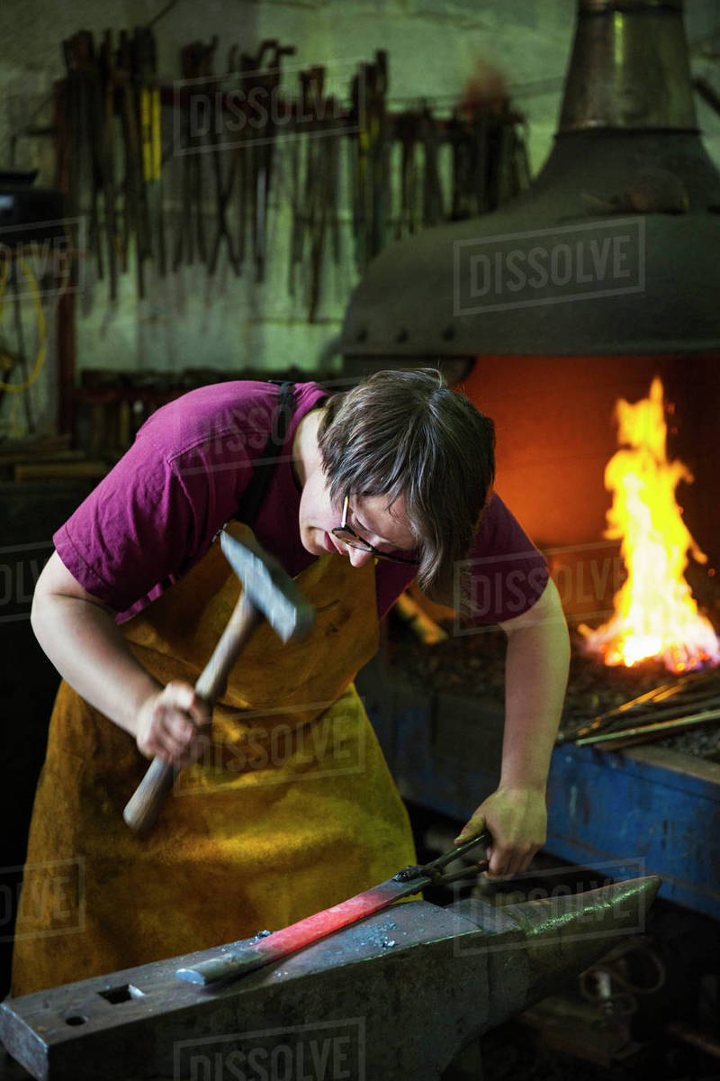 A blacksmith strikes a length of red hot metal on an anvil with a hammer in  a workshop  stock photo
