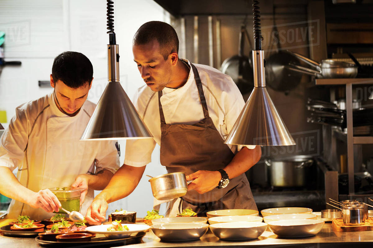 Two chefs standing in a restaurant kitchen plating food