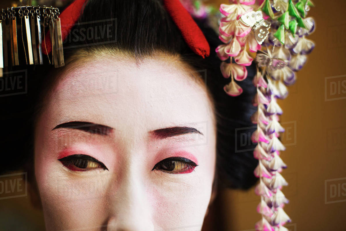 A woman made up in traditional geisha style with an elaborate hairstyle and  floral hair clips, drawn eyebrows with white face makeup with bright red  lips ...