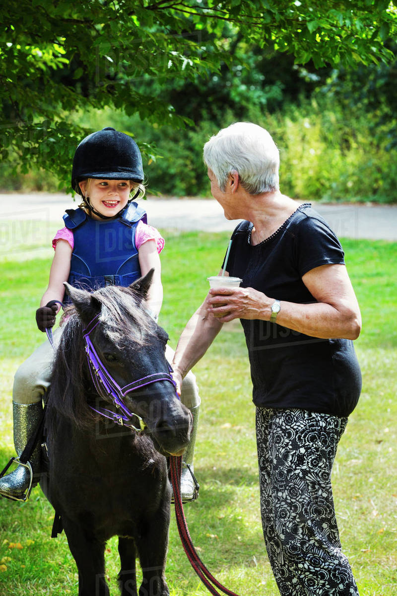 Woman And Blond Girl Wearing Riding Hat Sitting On A D102478004