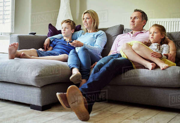 A family of four people, parents and a girl and boy, seated on the sofa together, watching television.  Royalty-free stock photo