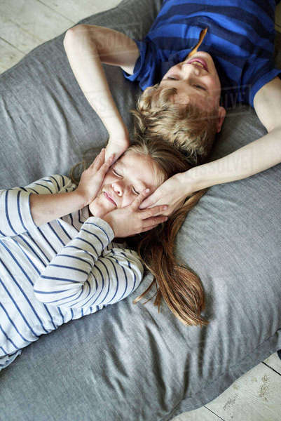 A family home.  A boy and girl lying on the sofa with their heads close together. View from above. Royalty-free stock photo