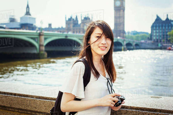 Young Japanese woman enjoying a day out in London, standing on the Queen's Walk by the River Thames. Royalty-free stock photo