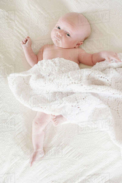 A baby boy lying on his back on a bed.  Royalty-free stock photo