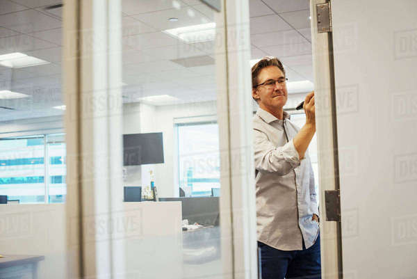 A man standing in an office writing on a whiteboard, seen through a doorway. Royalty-free stock photo