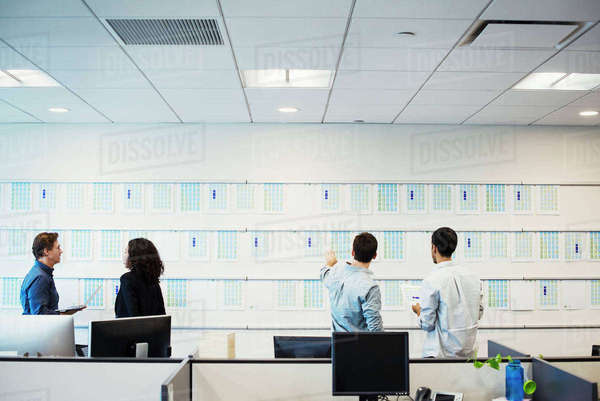 A woman and three men standing in an office looking at a display on a wall, seen from behind. Royalty-free stock photo