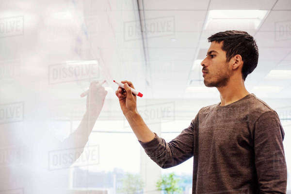 A man standing in a classroom writing on a whiteboard. Royalty-free stock photo