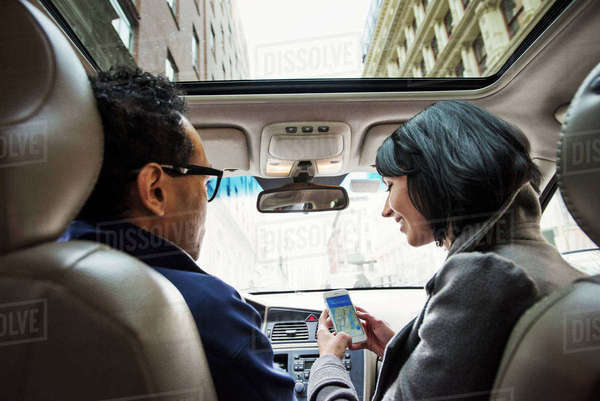 A young woman and young man in a car looking at a map on the display of a cellphone, seen from the back seat. Royalty-free stock photo