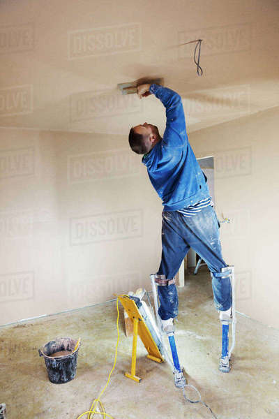 A plasterer wearing stilts smoothing fresh plaster high up on the walls of a house under construction.  Royalty-free stock photo