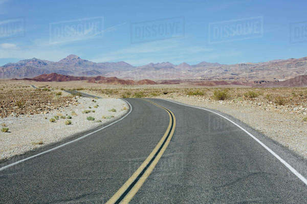 Curving road through desert, near Death Valley National Park, USA. Royalty-free stock photo