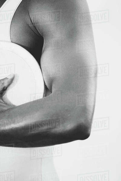 A female track and field athlete holding a discus in her hand.  Royalty-free stock photo