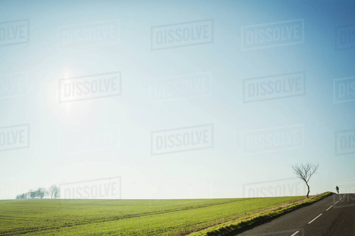 A man riding a road bike on a country road, silhouette on the brow of a  hill  Disappearing into the distance  stock photo