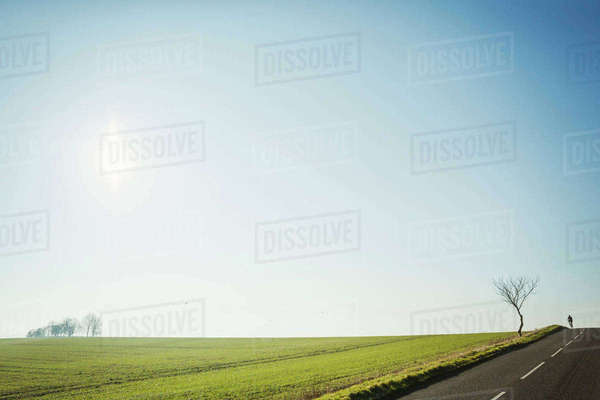 A man riding a road bike on a country road, silhouette on the brow of a hill. Disappearing into the distance.  Royalty-free stock photo