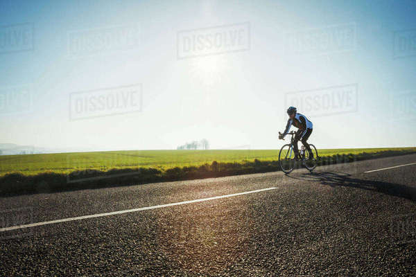 A cyclist riding along a country road on a clear sunny winter day.  Royalty-free stock photo