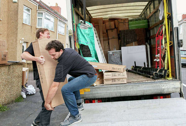 Removals business. Two men lifting an awkward package onto a van.   Royalty-free stock photo