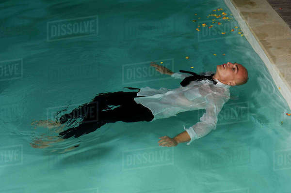 Man wearing trousers, shorts and tie floating on his back in swimming pool. Royalty-free stock photo