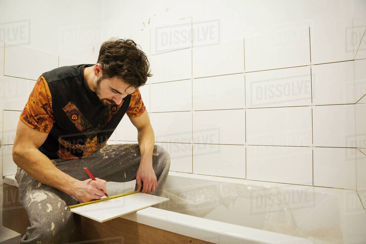 A builder, tiler working in a bathroom, marking a tile with a pencil ...