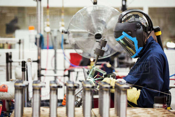 A person wearing a protective helmet using a welding torch in the assembly process in a cycle factory. A large fan cooling the heated metals.  Royalty-free stock photo