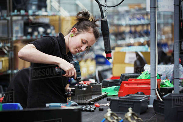 A young woman using a power tool, a skilled factory worker assembling cycle parts. Royalty-free stock photo