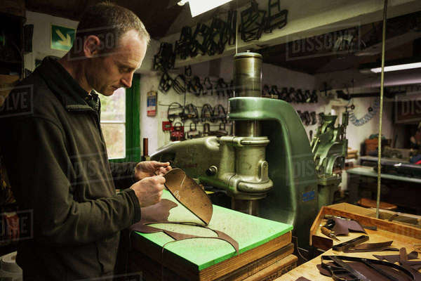Man standing in a shoemaker's workshop, cutting brown leather. Royalty-free stock photo