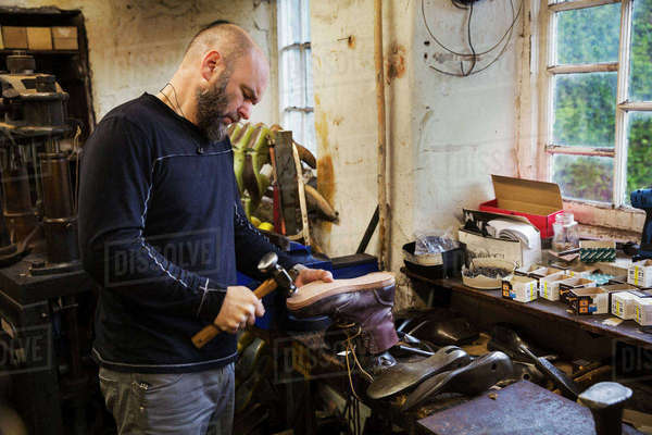 Man standing in a shoemaker's workshop by a window, using a hammer on the soles of a work boot. Royalty-free stock photo