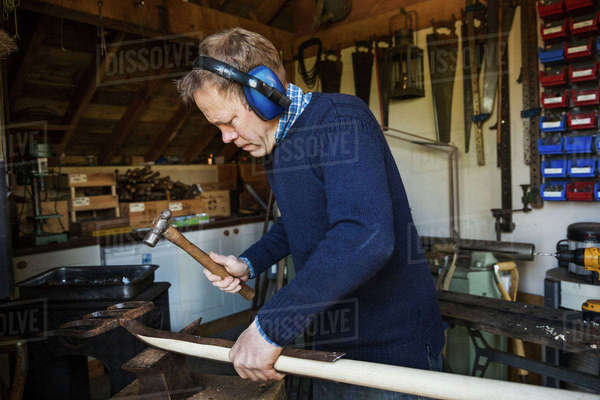 Man standing in a workshop, wearing ear protectors, holding a hammer, working on a piece of wood. Royalty-free stock photo
