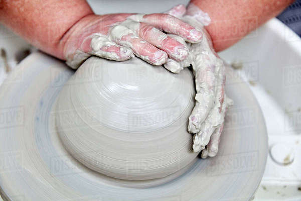 A person using a turning pottery wheel to throw a pot using clay, hands moulding the wet clay. Initial stage of throwing a pot. Royalty-free stock photo