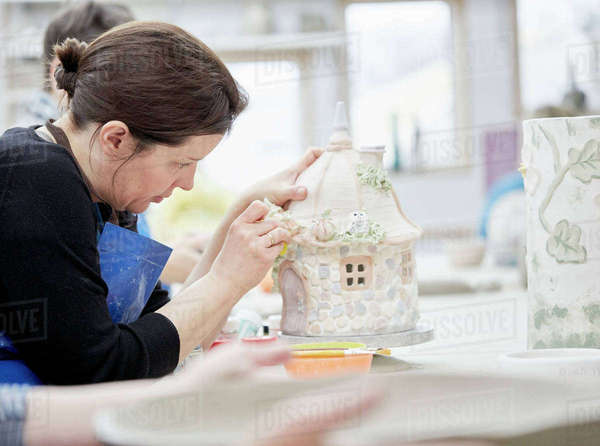 A woman working on a decorated pottery cottage with a sponge, decorating or finishing a piece.  Royalty-free stock photo