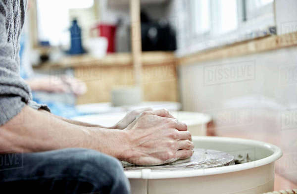 A man using a pottery wheel, with his hands on the clay, throwing pots in a pottery studio.  Royalty-free stock photo