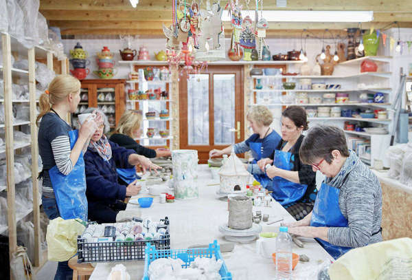 A group of people seated at a workbench in a pottery workshop, handbuilding clay objects. A woman with a cup of tea.  Royalty-free stock photo