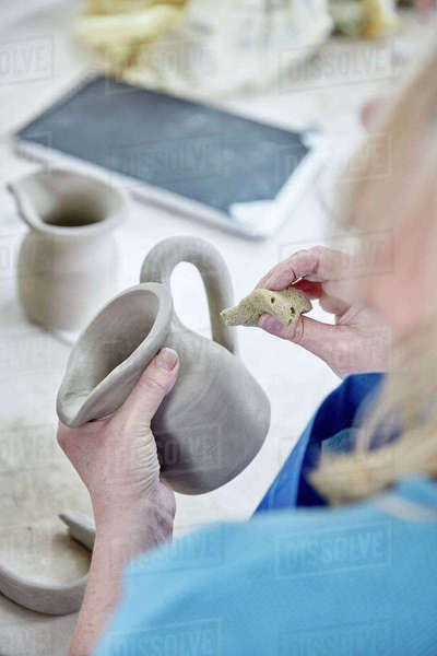A woman using her hands to shape and smooth a wet clay jug to match another, making a pair.  Royalty-free stock photo