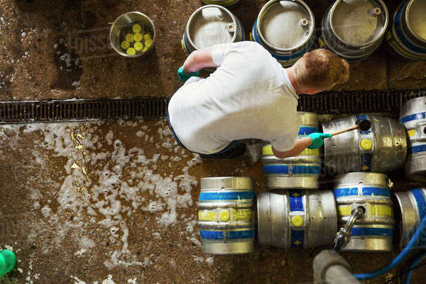 Directly above view of a man working in a brewery, metal beer kegs standing on the floor. Royalty-free stock photo