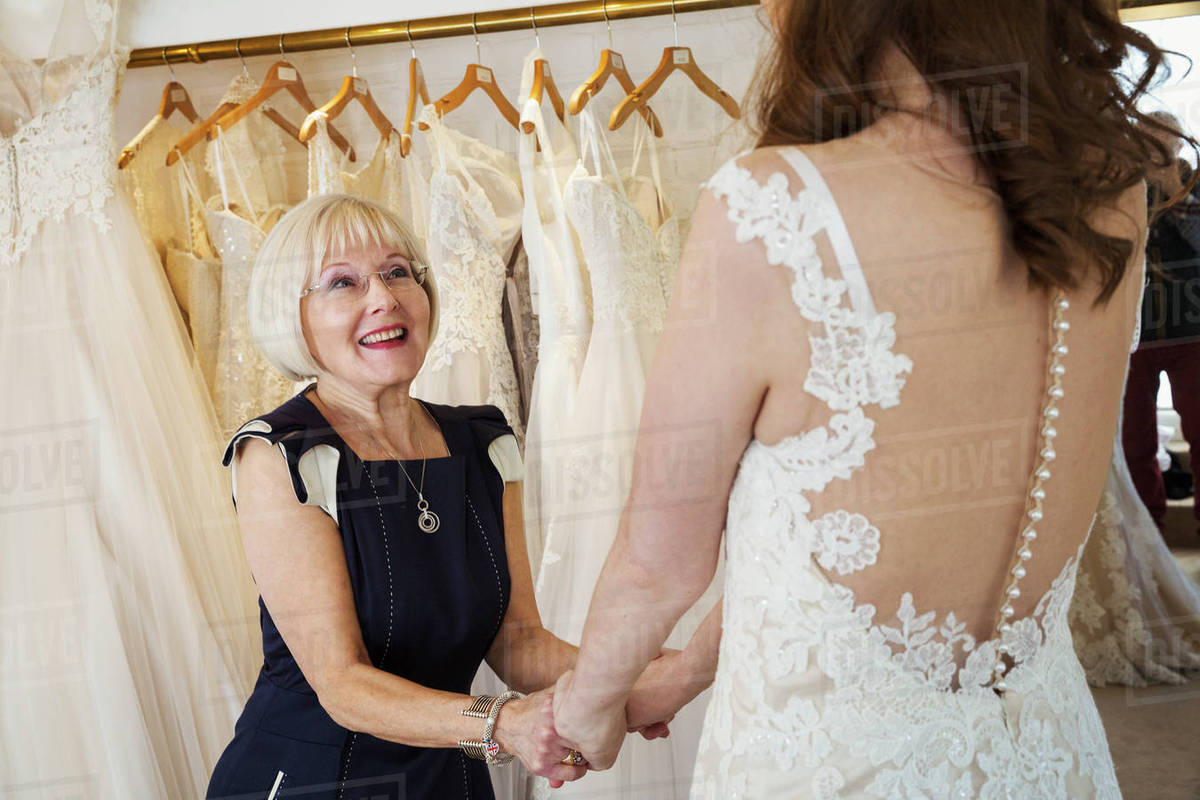A Woman Bride To Be Trying On Dresses With The Help Of S Istant In Wedding Dress