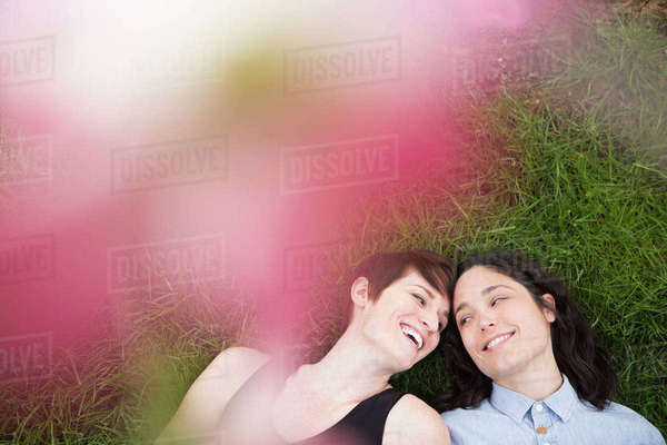 A same sex couple, two women lying on the grass laughing, under the branches of a flowering tree.  Royalty-free stock photo