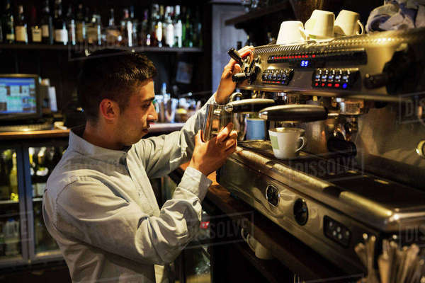 Side view of man standing at an espresso machine, frothing milk. Royalty-free stock photo