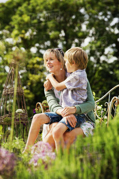 Woman sitting in a garden with a boy on her lap, hugging. Royalty-free stock photo