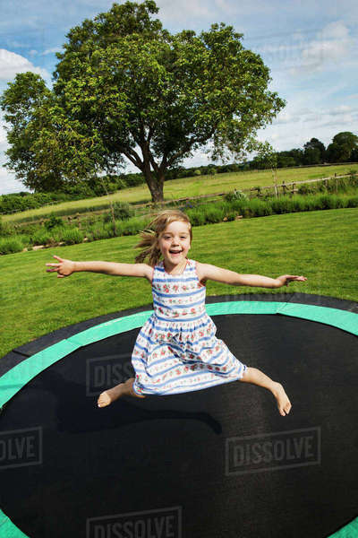 Girl in a sundress jumping on a trampoline in a garden. Royalty-free stock photo