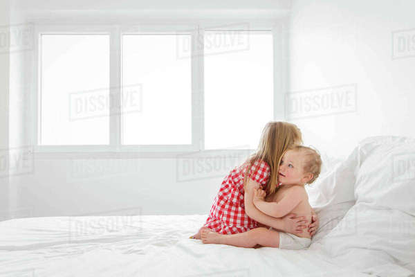 Blond girl wearing red and white checkered dress sitting on bed, hugging baby boy. Royalty-free stock photo