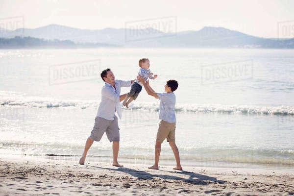 Man and boy wearing shorts standing on a sandy beach by the ocean, holding aloft young boy, playing. Royalty-free stock photo