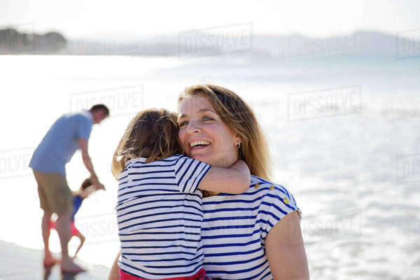 Smiling blond woman wearing stripy T-shirt standing on beach, holding girl, man in the background. Royalty-free stock photo