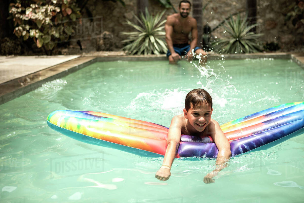 A boy floating on a pool raft in a swimming pool. stock photo
