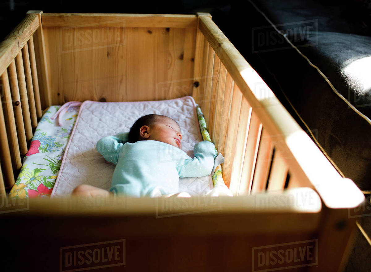 High angle view of small baby lying on her back in a crib. - Stock ... c4c9cfec426f