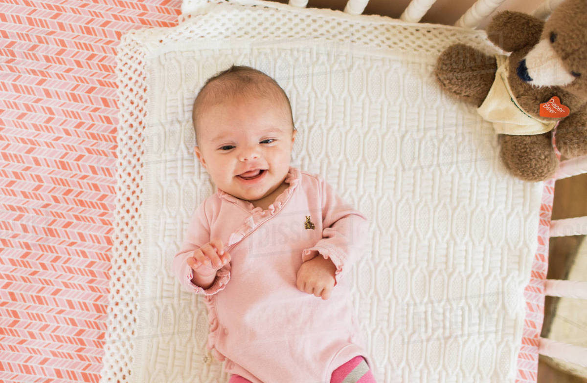 High angle view of smiling baby wearing pink onesie lying on her back 60a34f7e8c11