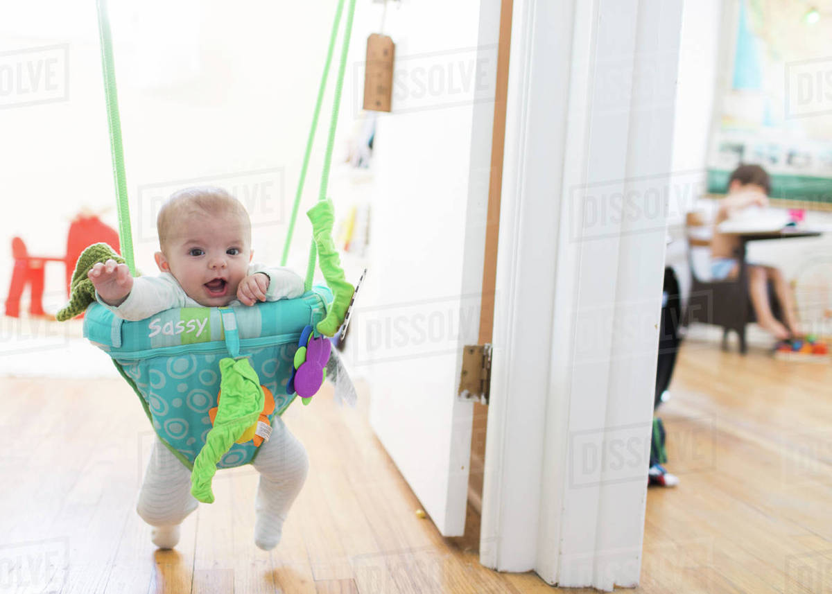 3ad2af82a A baby girl standing in a baby bouncer hanging in a doorway. - Stock ...