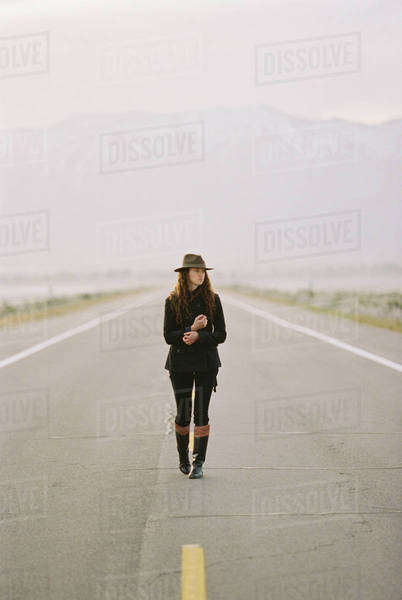 A woman walking down the middle of a country road, wearing a hat and carrying a backpack. Royalty-free stock photo