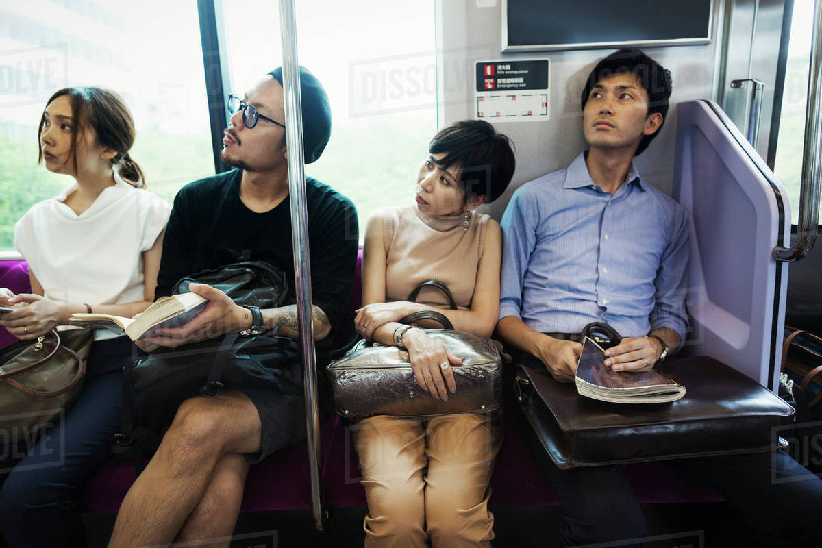 Four people sitting sidy by side on a subway train, Tokyo ...